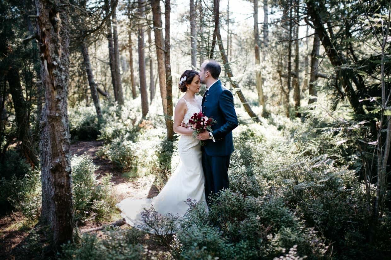 Brautpaar steht mitten im Wald und Bräutigam gibt der Braut einen Kuss auf die Stirn