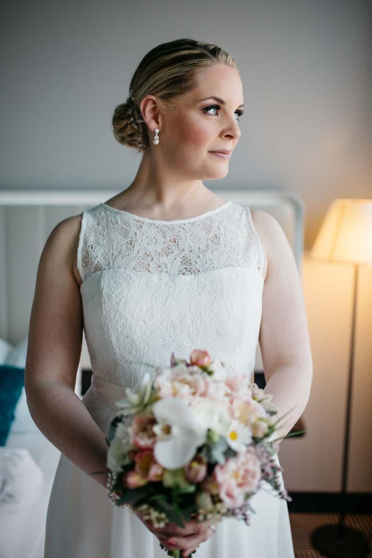 Brautportrait mit Brautstrauß vor dem Fenster