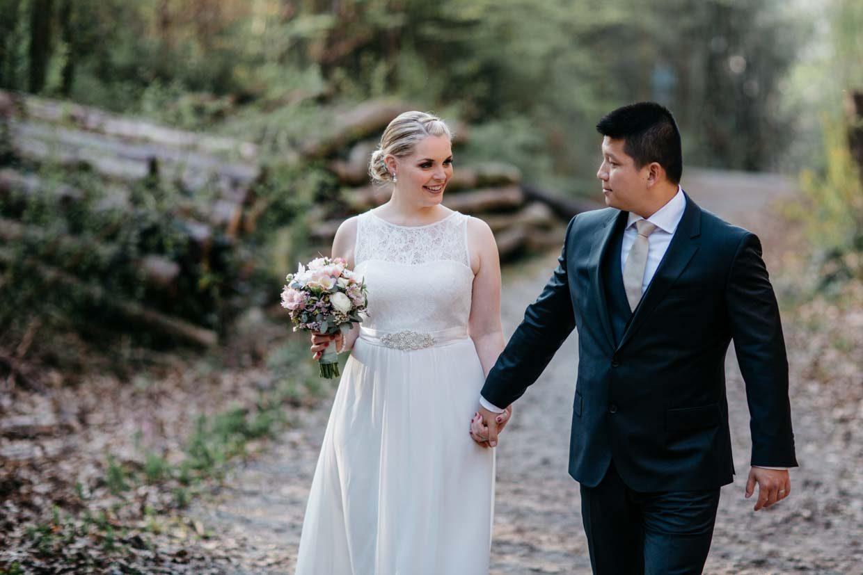 Brautpaar geht entspannt beim Brautpaarshooting und schaut sich an