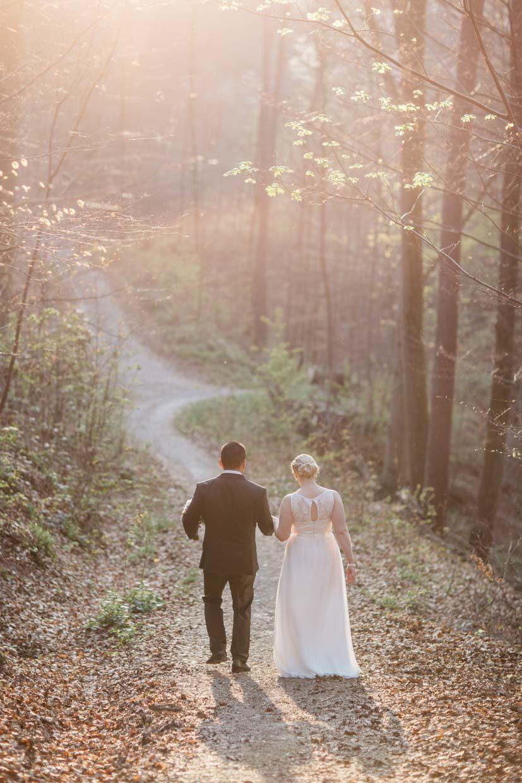 Brautpaar im Wald von hinten mit schöner Gegenlichtstimmung und untergehender Sonne