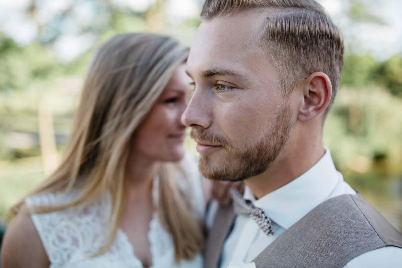 Bräutigam im Vordergrund und die Braut im Hintergrund