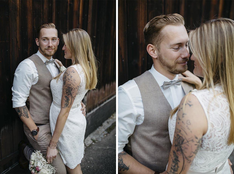 Bräutigam lehnt an einer Holzwand und Braut steht vor ihm