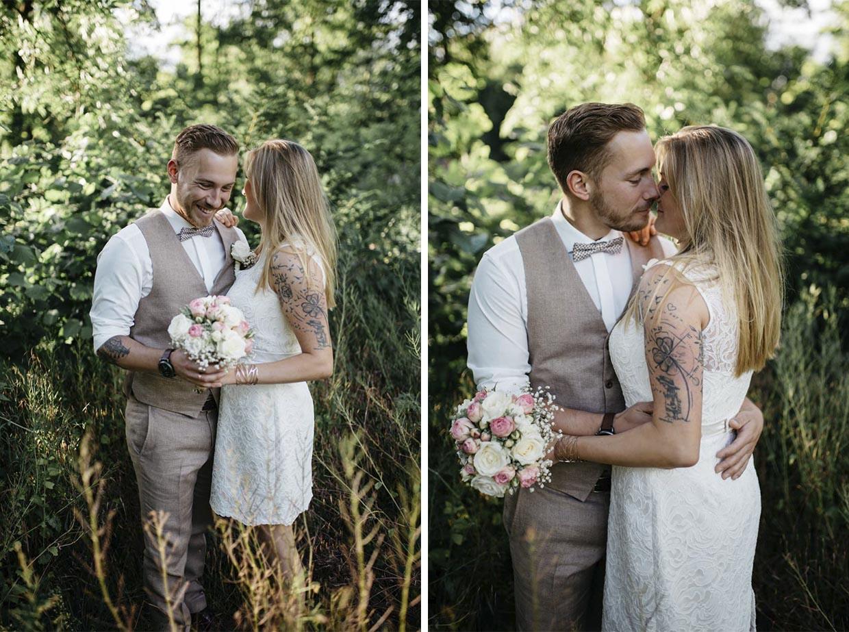 Brautpaar steht in einem Feld, lacht und küsst sich
