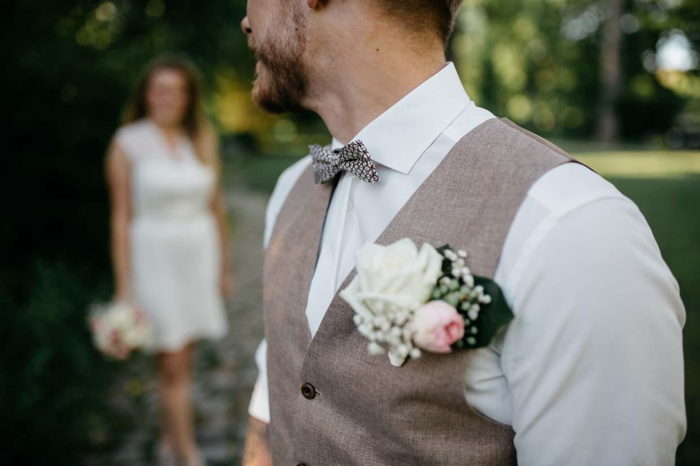 Detailaufnahme des Anzuges des Bräutigams und im Hintergrund steht die Braut