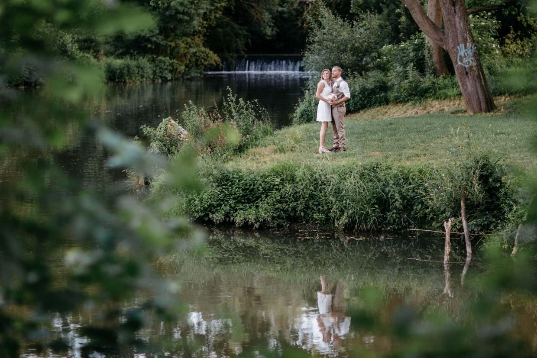 Brautpaar steht auf einer Wiese vor einem Fluss