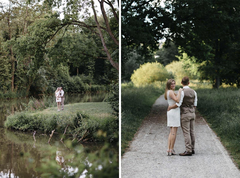 Brautpaar steht auf einer Wiese vor einem Fluss und auf einem Feldweg