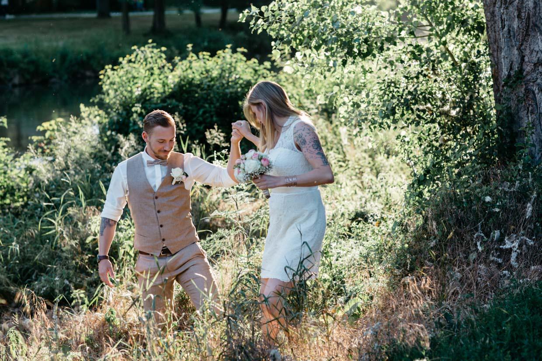 Bräutigam hilft der Braut beim reinlaufen in ein Feld