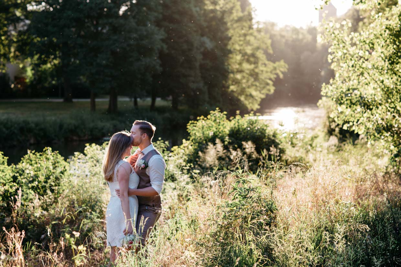 Brautpaar steht am Flussufer bei schönem Sonnenuntergang