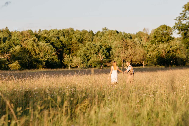 Brautpaar läuft durch ein Feld bei schönem Sonnenuntergang