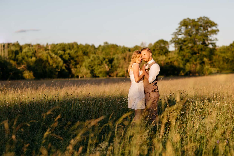 Brautpaar steht in einem Feld bei schönem Sonnenuntergang