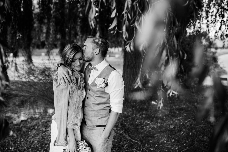 Brautpaar steht unter einem Baum und Bräutigam küsst die Braut auf die Stirn