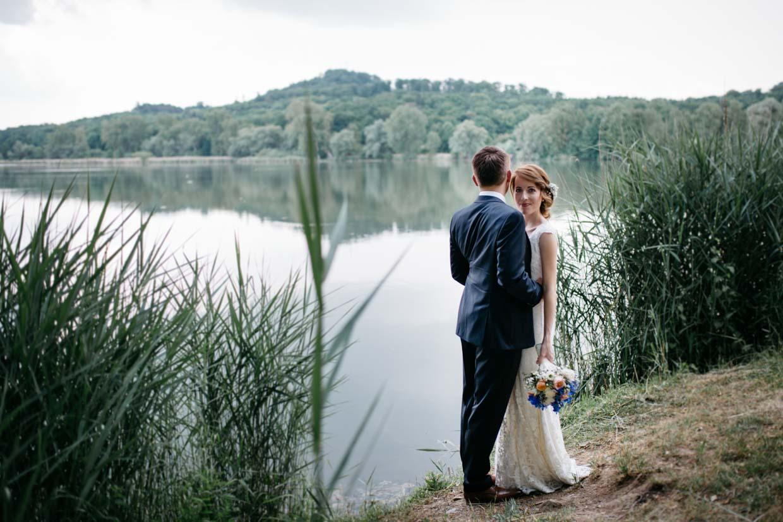 Brautpaar stehr vor einem See und Braut schaut in die Kamera