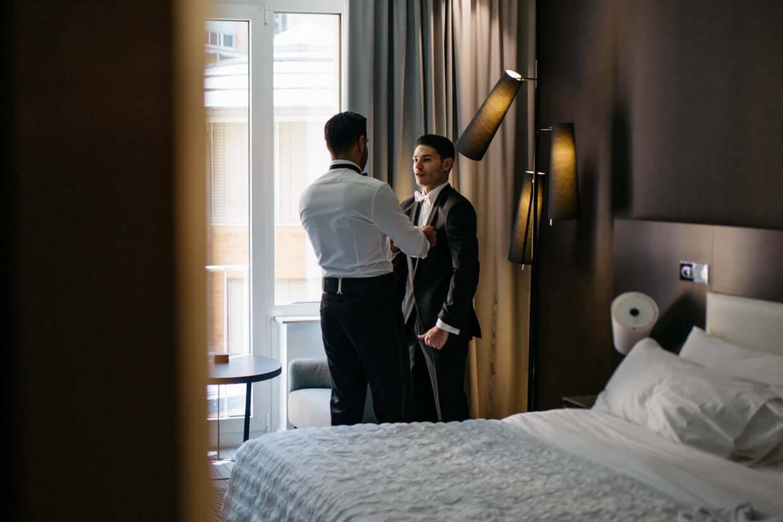 Trauzeuge hilft Bräutigam beim Anziehen des Sakkos