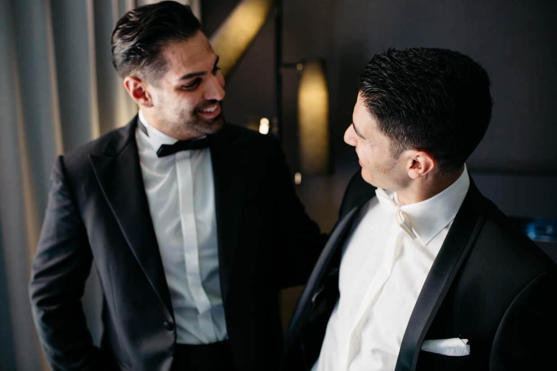 Bräutigam und Trauzeuge schauen sich an und lachen