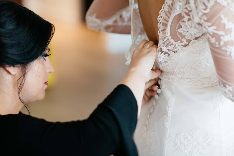 Trauzeugin knöpft Brautkleid von hinten zu