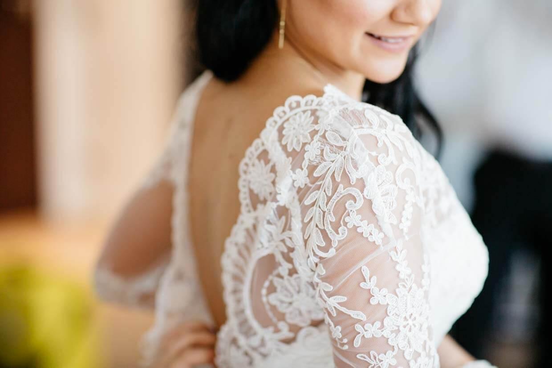 Detailaufnahme beim Anziehen des Brautkleides