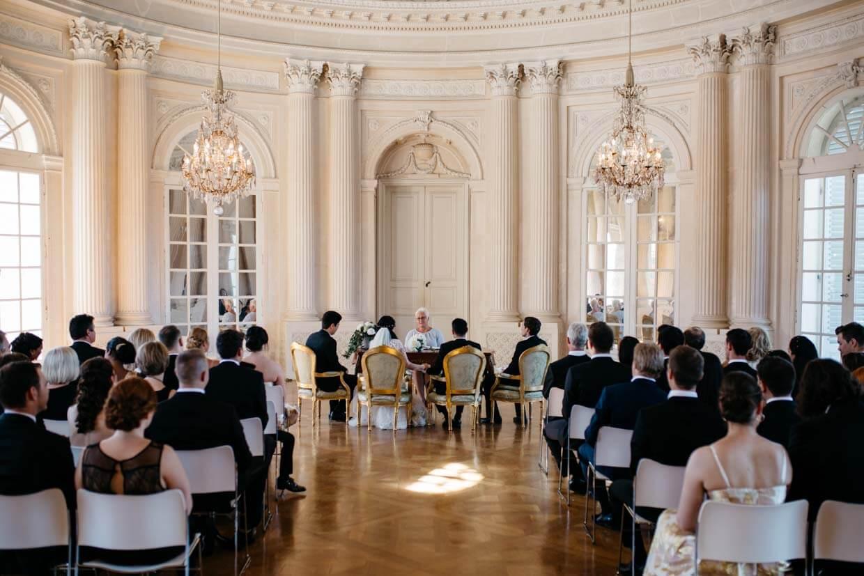 Brautpaar und Hochzeitsgäste bei der Trauung von hinten fotografiert