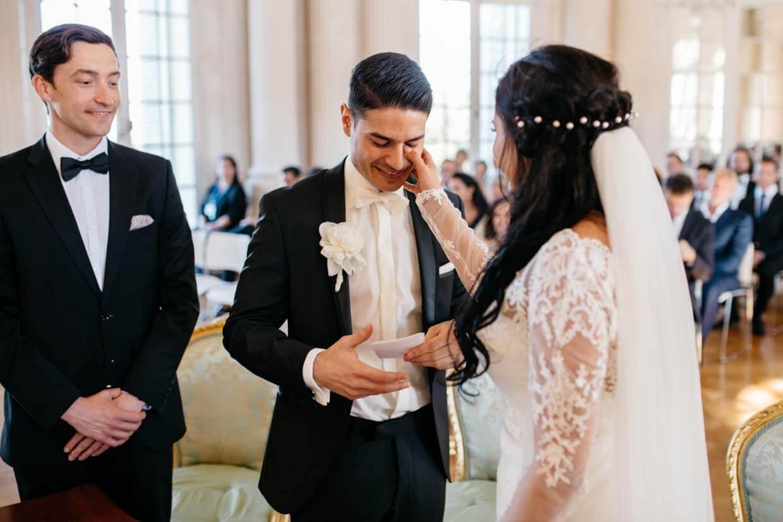 Braut wischt gerührtem Bräutigam Träne aus dem Gesicht