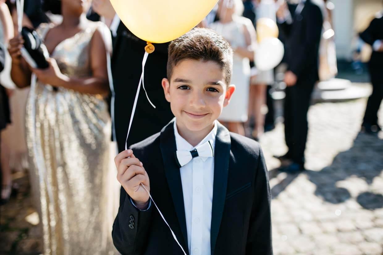 kleiner Junge hält gelben Luftballon und schaut in die Kamera