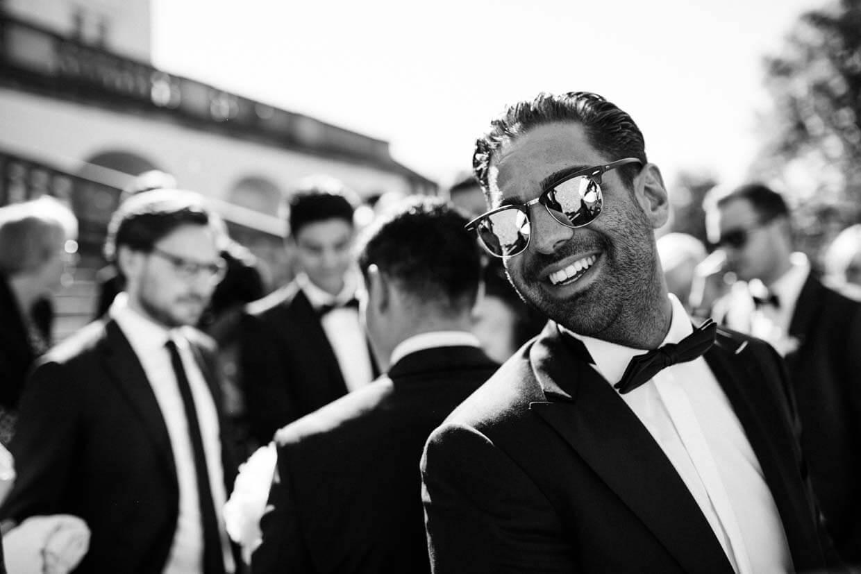 Hochzeitsgast mit Sonnenbrille schaut in die Kamera und lacht