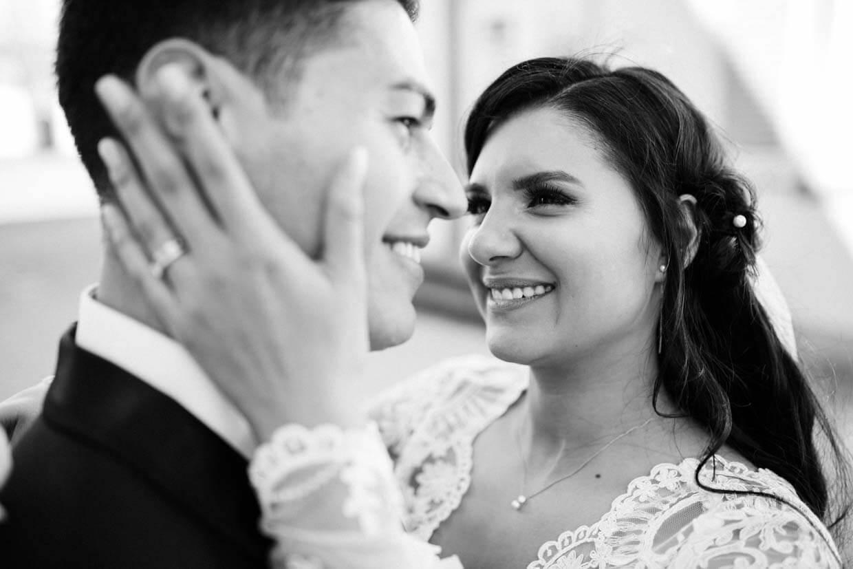 Braut hält den Kopf des Bräutigams und schaut ihn liebevoll an