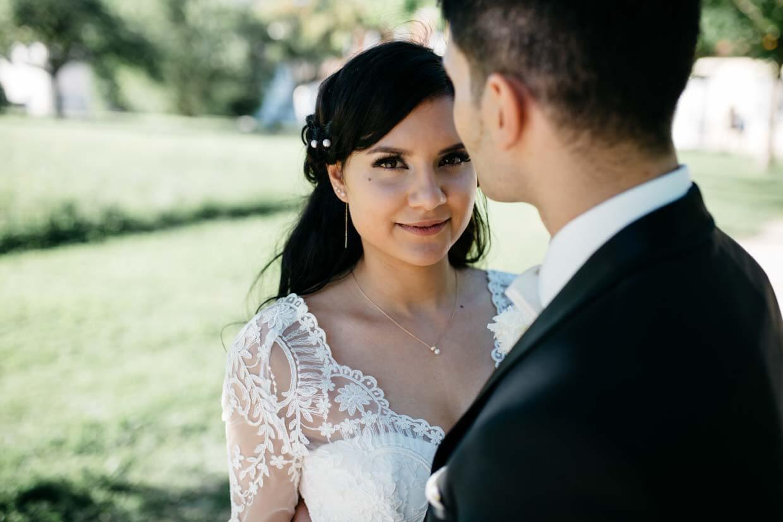 Braut schaut über die Schulter des Bräutigams in die Kamera
