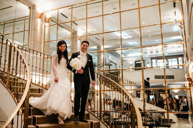 Brautpaar kommt eine große vergoldete Wendeltreppe hinunter