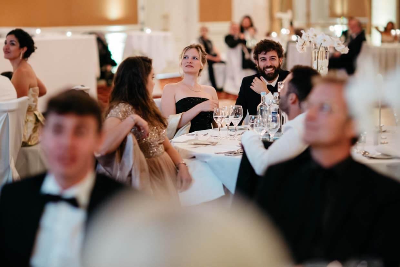 Hochzeitsgäste unterhalten sich und lachen am Tisch