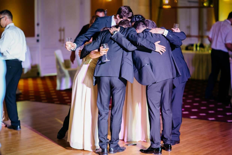Hochzeitsgäste stehen im Kreis und machen ein Foto mit dem Smartphone auf dem Boden