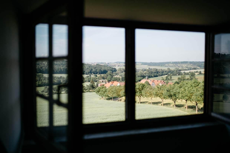 Blick durch offene Holzfenster in das Dorf