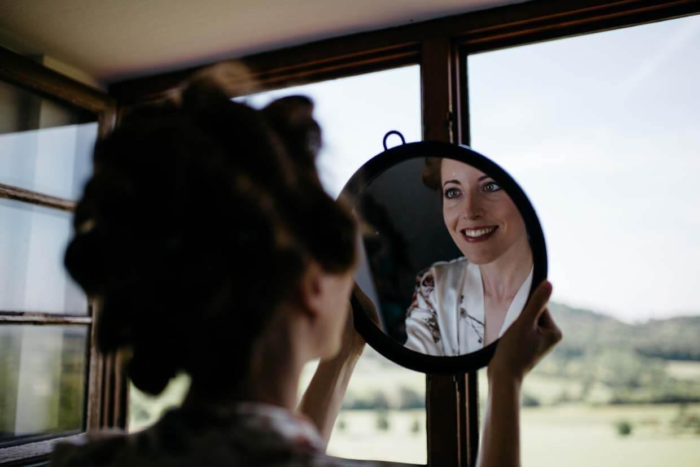 Braut steht vor einem Holzfenster und schaut sich in einem runden Spiegel an