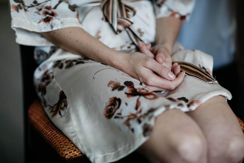 Braut sitzt auf einem Stuhl und hält die Hände zusammen