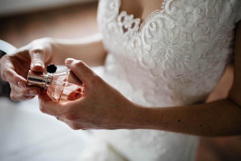 Braut hält Parfümflasche in den Händen