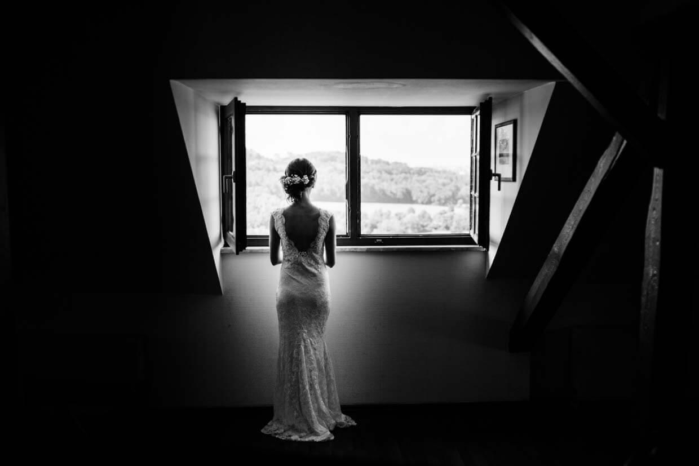 Braut steht vor offenem Holzfenster