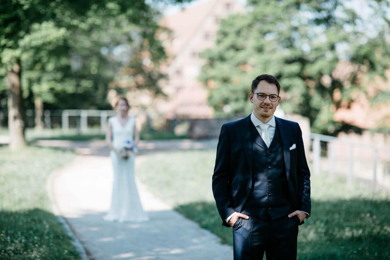 Bräutigam wartet auf die Braut, die im Hintergrund steht