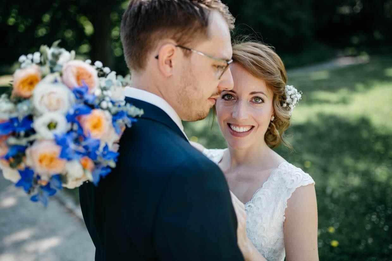 Braut hält Brautstrauß um den Hals des Bräutigams und lächelt