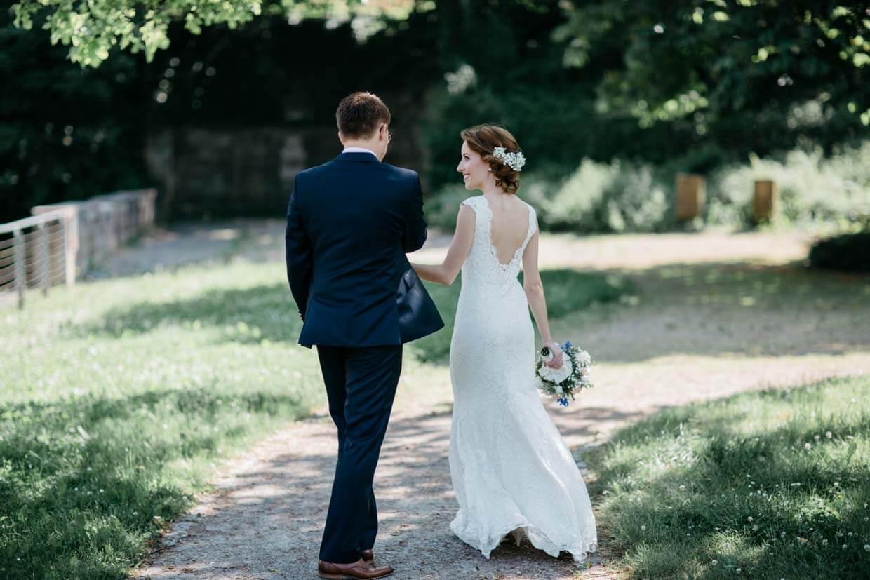 Brautpaar geht auf einem Weg und lacht sich an