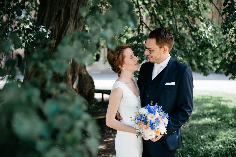 Brautpaar steht unter einem Baum und schaut sich an