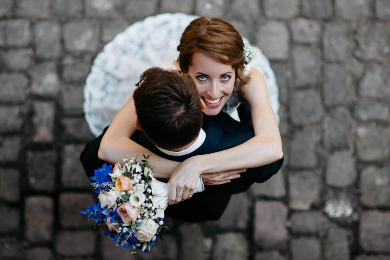 Braut umarmt den Bräutigam um den Hals und wird von oben fotografiert