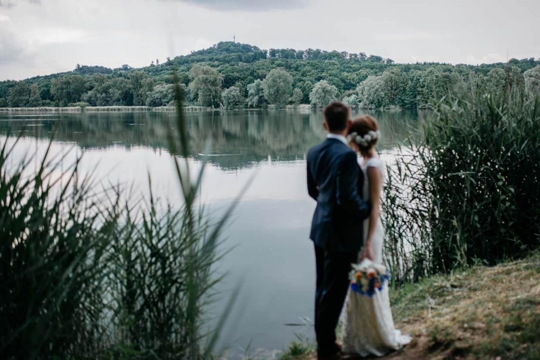 Brautpaar stehr vor einem See