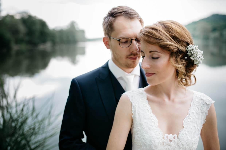 Brautpaar stehr vor einem See mit geschlossenen Augen