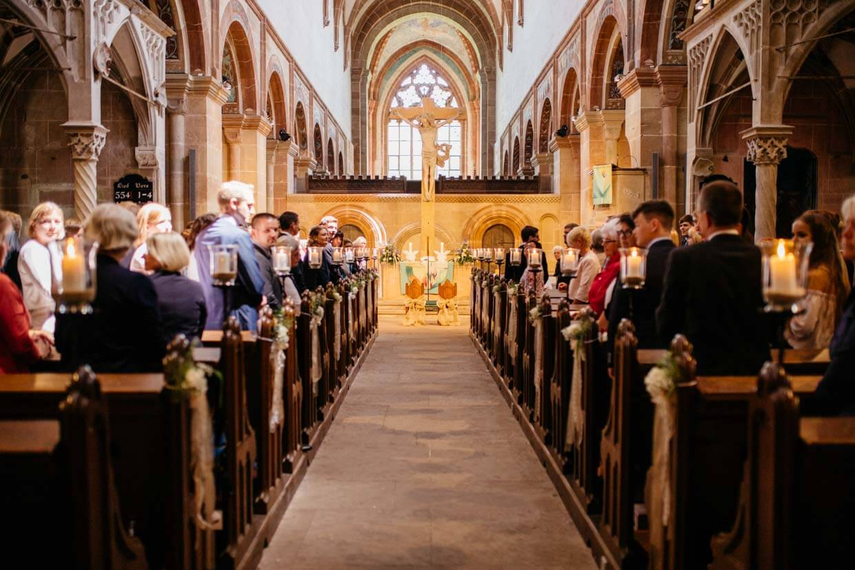 Hochzeitsgäste stehen in der Kirche und warten auf das Brautpaar