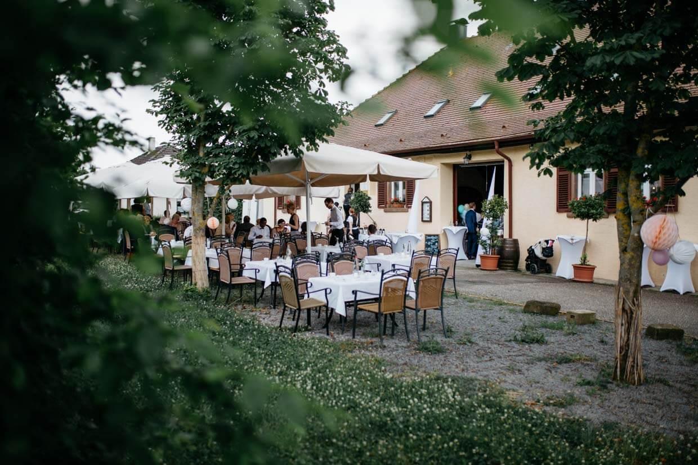 Hochzeitsgäste sitzen draußen im Garten
