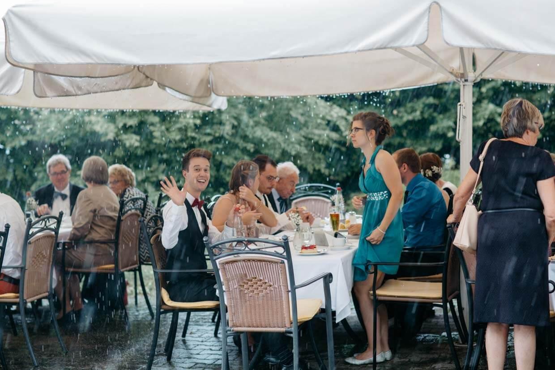 Hochzeitsgäste sitzten unter Schirmen beim Regen
