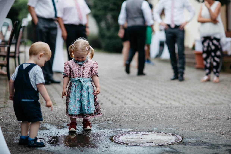 Kleinkinder spielen in einer Pfütze