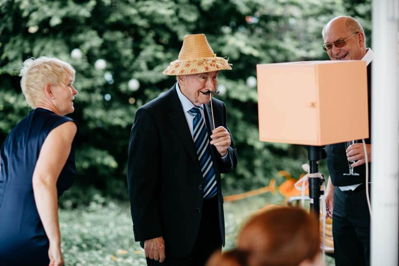 Älterer Herr macht ein Foto vor einer Fotobox