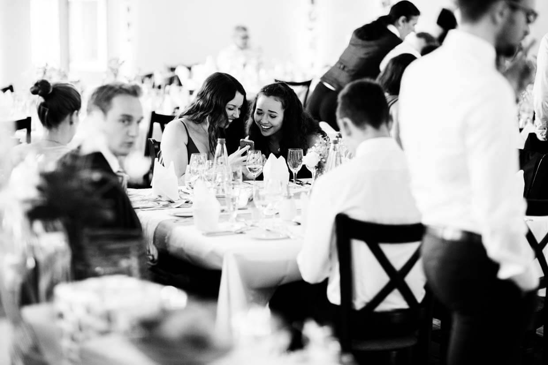 Hochzeitsgäste sitzen am Tisch und lachen