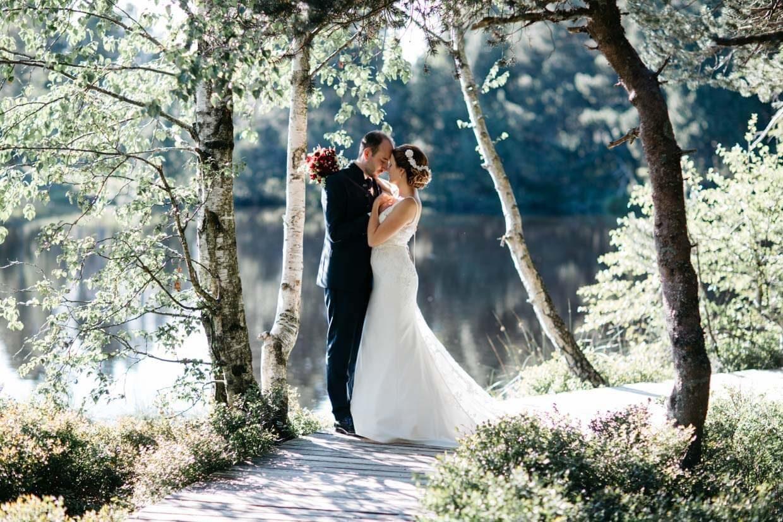 Brautpaar steht eng umschlungen auf einem Steg vor einem See