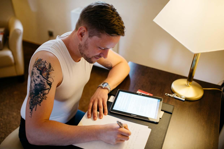 Bräutigam sitzt am Tisch und schreibt seine Rede