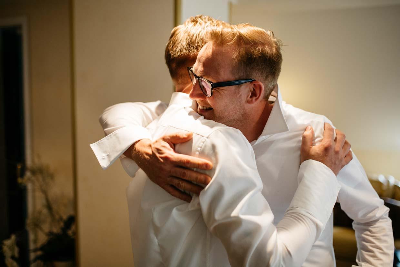 Trauzeuge umarmt den Bräutigam